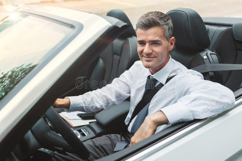Homem de negócios bem sucedido que conduz seu carro foto de stock royalty free