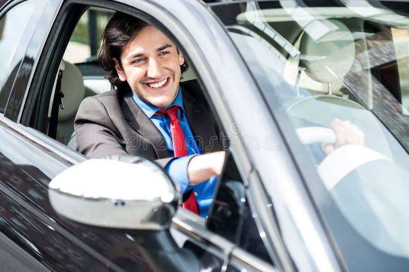 Homem de negócios bem sucedido que conduz um carro luxuoso imagens de stock