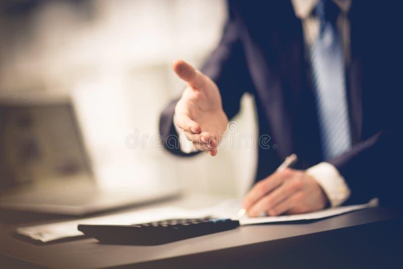Homem de negócios bem sucedido que dá uma mão fotografia de stock