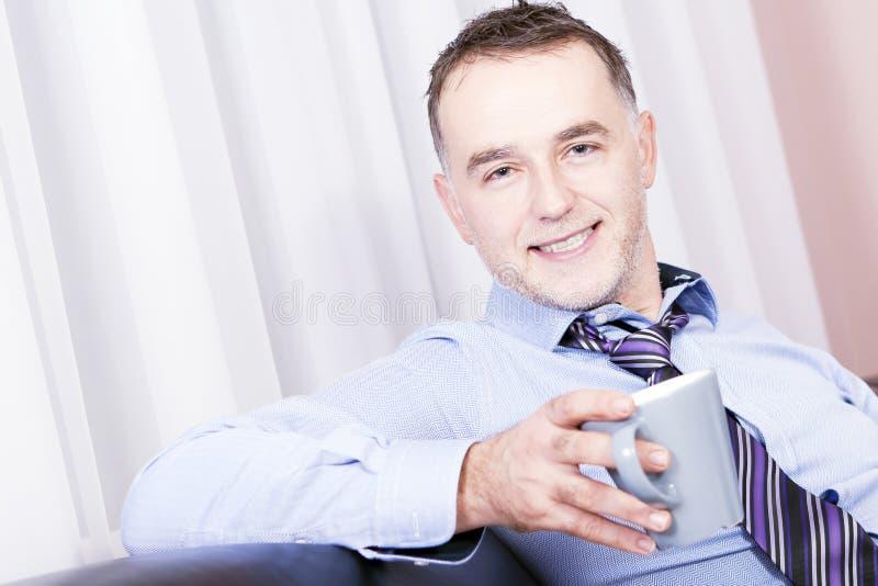 Homem de negócios bem sucedido que relaxa em casa. fotografia de stock