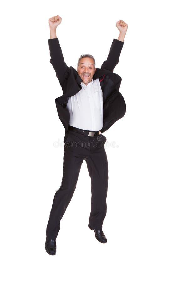 Homem de negócios bem sucedido que salta com as mãos levantadas imagem de stock royalty free