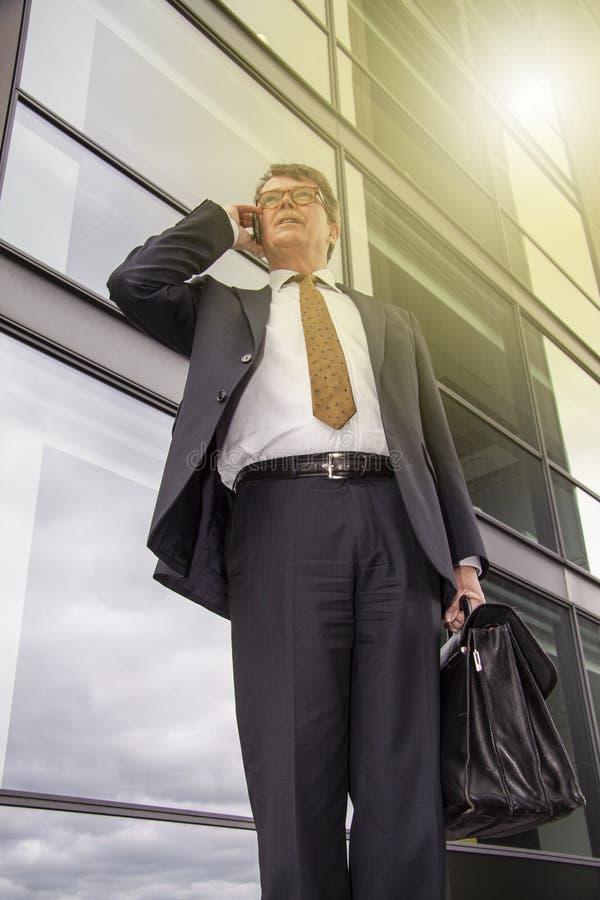 Homem de negócios bem vestido com posição da pasta que fala no telefone na frente da construção de vidro moderna com reflexão do  fotos de stock royalty free