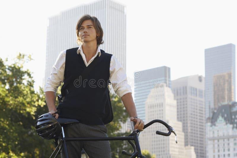 Homem de negócios With Bicycle Standing no parque da cidade imagens de stock royalty free