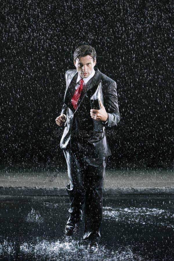 Homem de negócios With Binder Running na chuva imagem de stock