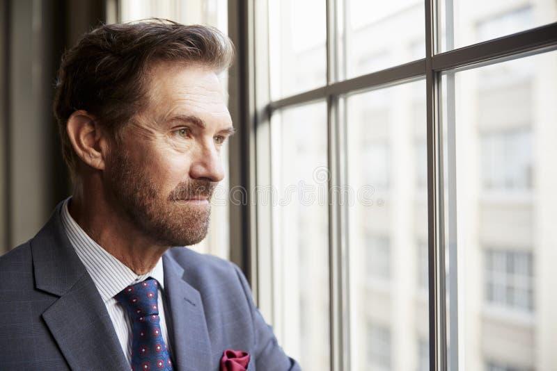 Homem de negócios branco superior que olha fora da janela, fim acima fotos de stock royalty free