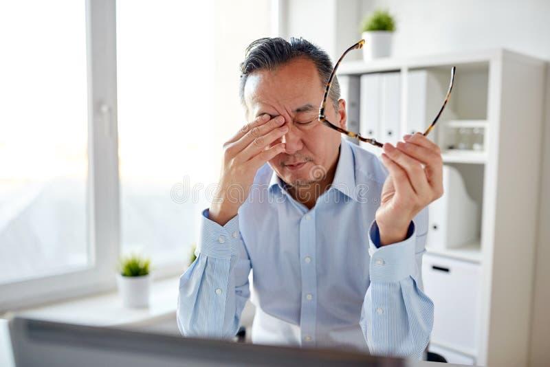 Homem de negócios cansado com vidros no portátil no escritório imagem de stock