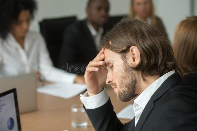 Homem de negócios cansado frustrante que tem a dor de cabeça forte em t diverso fotografia de stock
