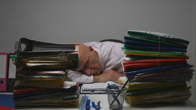 Homem de negócios cansado no arquivo explicando que dorme no trabalho foto de stock royalty free