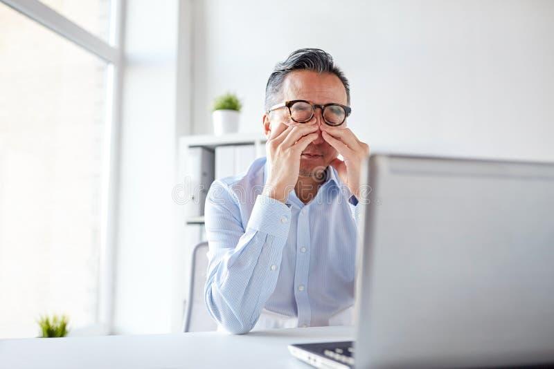 Homem de negócios cansado nos vidros com o portátil no escritório foto de stock