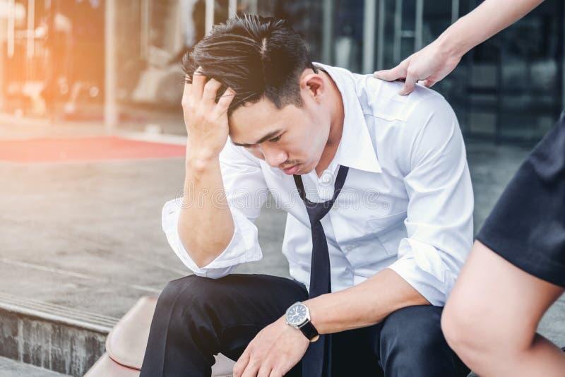 Homem de negócios cansado ou forçado que senta-se na passagem após o trabalho imagens de stock