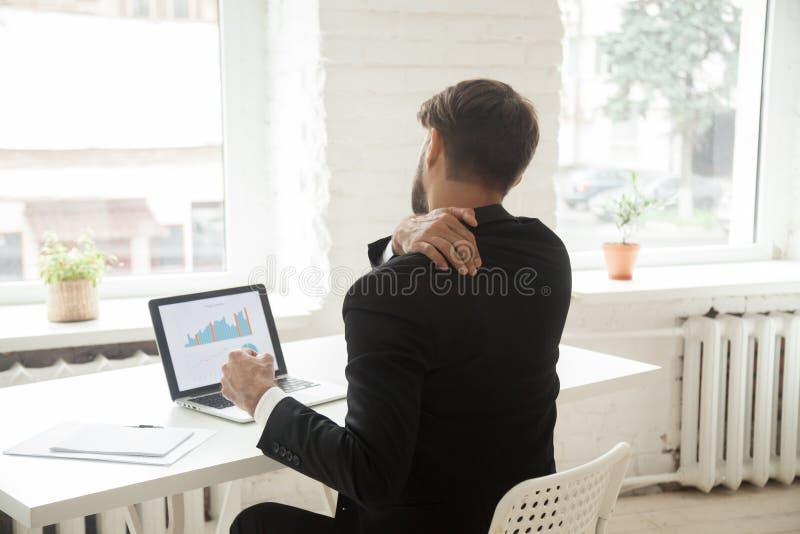 Homem de negócios cansado que estica no local de trabalho esgotado após o trabalho imagem de stock royalty free