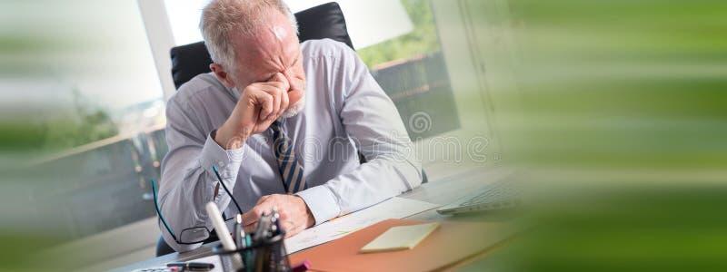 Homem de negócios cansado que fricciona seus olhos imagem de stock