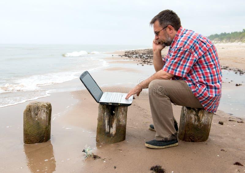Homem de negócios cansado que senta-se com o caderno na praia fotografia de stock royalty free