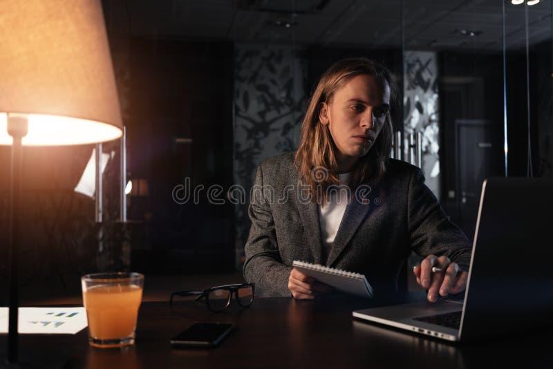 Homem de negócios cansado que trabalha pelo portátil contemporâneo no escritório da noite Moderno com o bloco de notas longo da p foto de stock