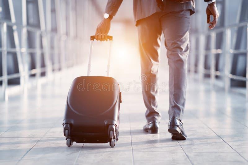 Homem de negócios Carrying Suitcase, andando através da ponte do embarque do passageiro imagem de stock