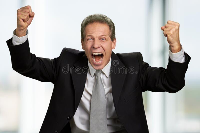 Homem de negócios caucasiano entusiasmado que comemora a vitória foto de stock