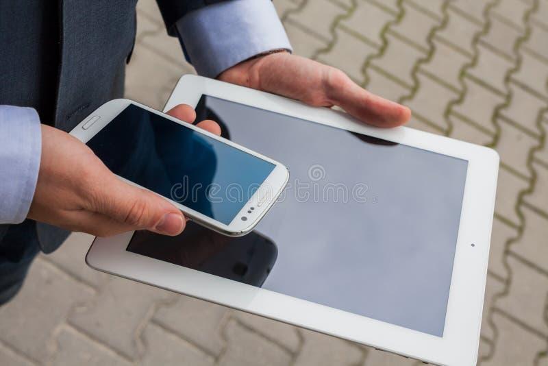 Homem de negócios caucasiano fora do escritório usando o PC branco da tabuleta na foto de stock