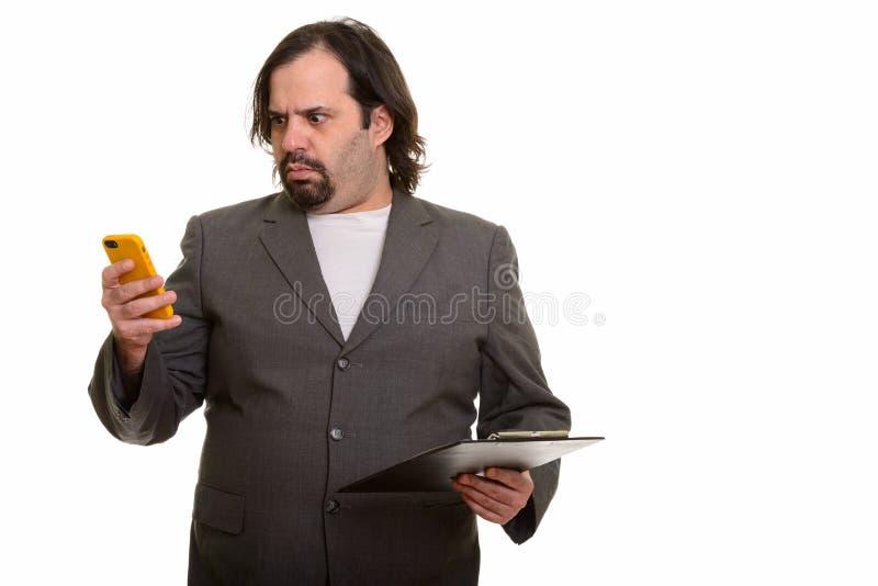 Homem de negócios caucasiano gordo que olha o quando forçado usando o pH móvel fotografia de stock