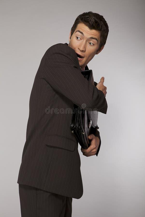 Homem de negócios caucasiano novo assustado e que defende sua pasta fotografia de stock
