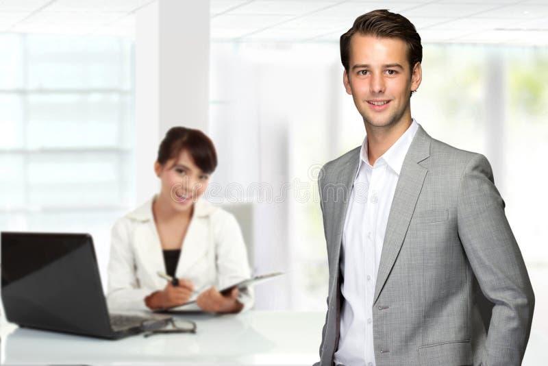 Homem de negócios caucasiano novo, com seu secretário atrás Isolado fotos de stock