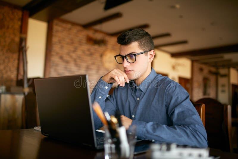 Homem de negócios caucasiano novo pensativo no funcionamento de vidros no laptop Freelancer atrativo pensativo do moderno fotos de stock royalty free