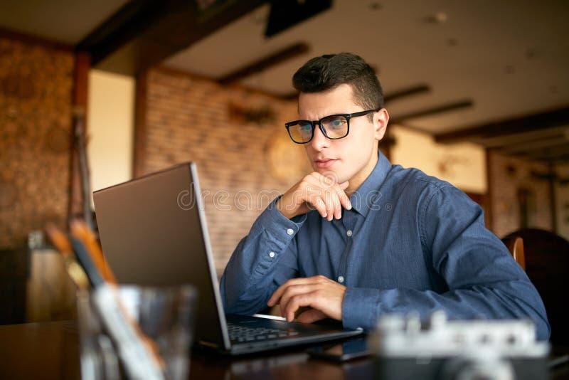 Homem de negócios caucasiano novo pensativo no funcionamento de vidros no laptop Freelancer atrativo pensativo do moderno foto de stock royalty free