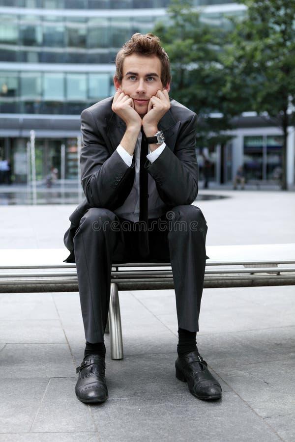 Homem de negócios caucasiano novo que senta-se no banco foto de stock royalty free