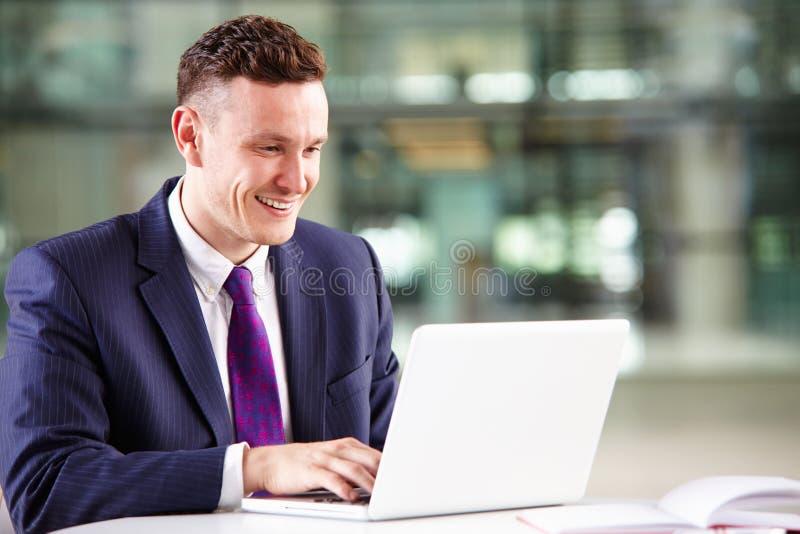Homem de negócios caucasiano novo que usa o laptop no trabalho imagens de stock