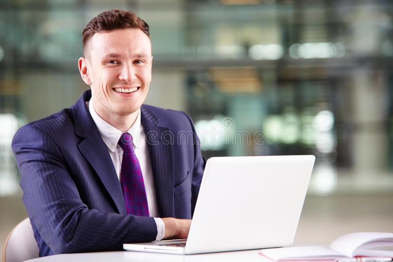 Homem de negócios caucasiano novo que usa o laptop no trabalho fotos de stock