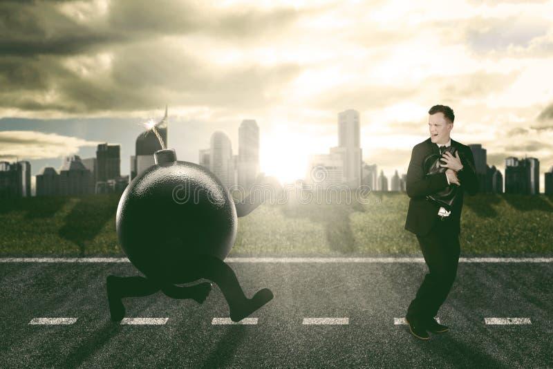 Homem de negócios caucasiano que corre afastado a perseguição por uma bomba foto de stock