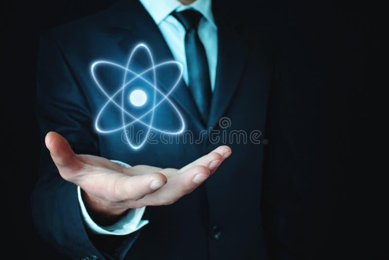 Homem de negócios caucasiano que guarda o átomo Poder e conceito da inovação foto de stock royalty free