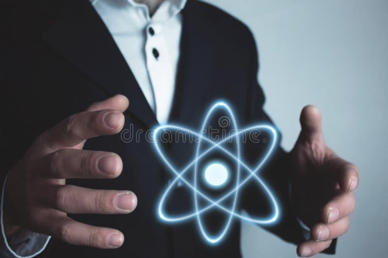 Homem de negócios caucasiano que guarda o átomo Poder e conceito da inovação fotografia de stock royalty free