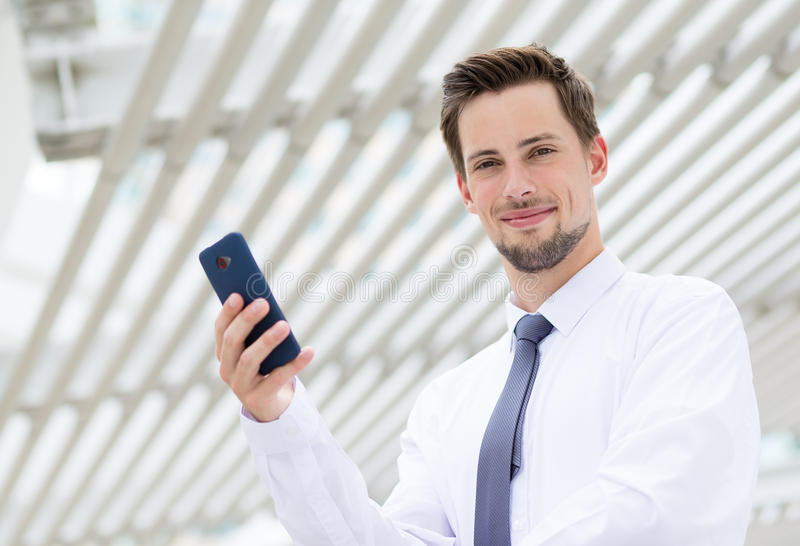 Homem de negócios caucasiano que guarda o telefone celular foto de stock royalty free