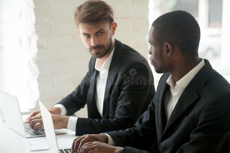 Homem de negócios caucasiano que olha o rival de negócio africano, rivalidade fotos de stock