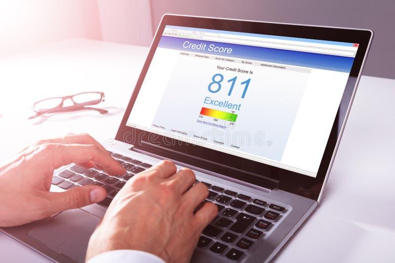 Homem de negócios Checking Credit Score no portátil fotos de stock