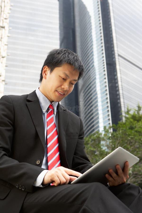 Homem de negócios chinês que trabalha no computador da tabuleta fotografia de stock royalty free