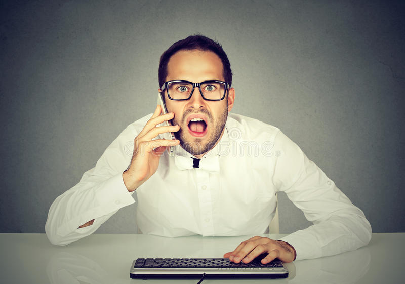 Homem de negócios chocado que fala no telefone ao usar o computador fotos de stock