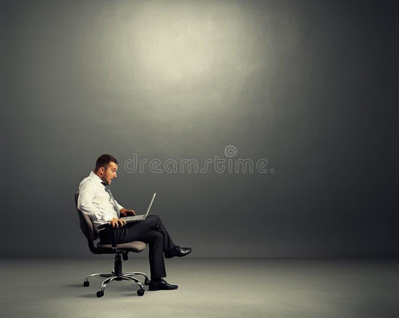 Homem de negócios chocado que olha o portátil foto de stock