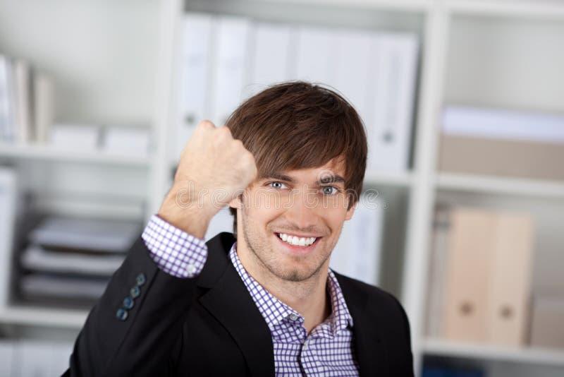 Homem de negócios With Clenched Fist no escritório imagens de stock
