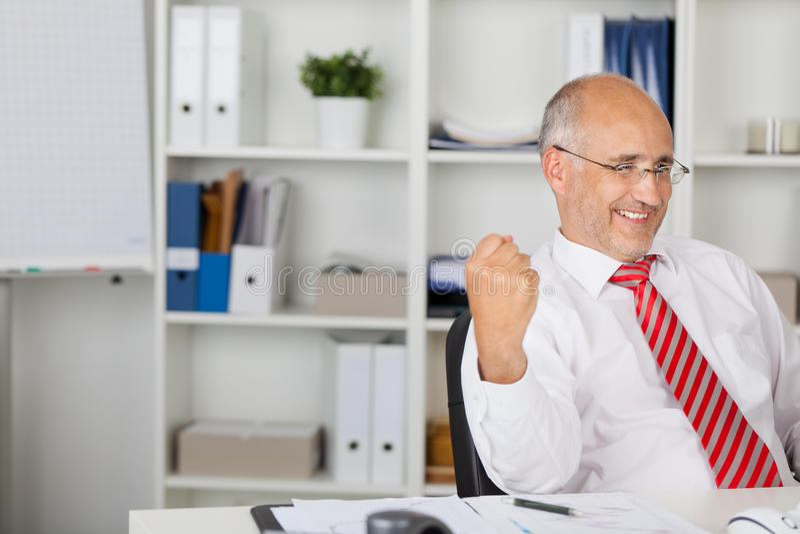 Homem de negócios With Clenched Fist que comemora Victory At Desk foto de stock royalty free