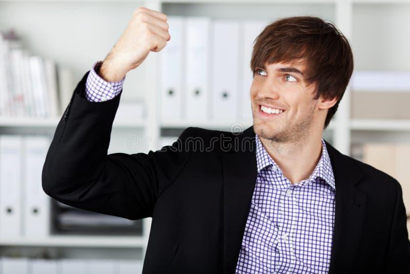 Homem de negócios With Clenched Fist que comemora Victory In Office fotografia de stock