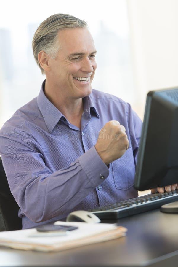 Homem de negócios With Clenched Fist que olha o computador no escritório fotografia de stock