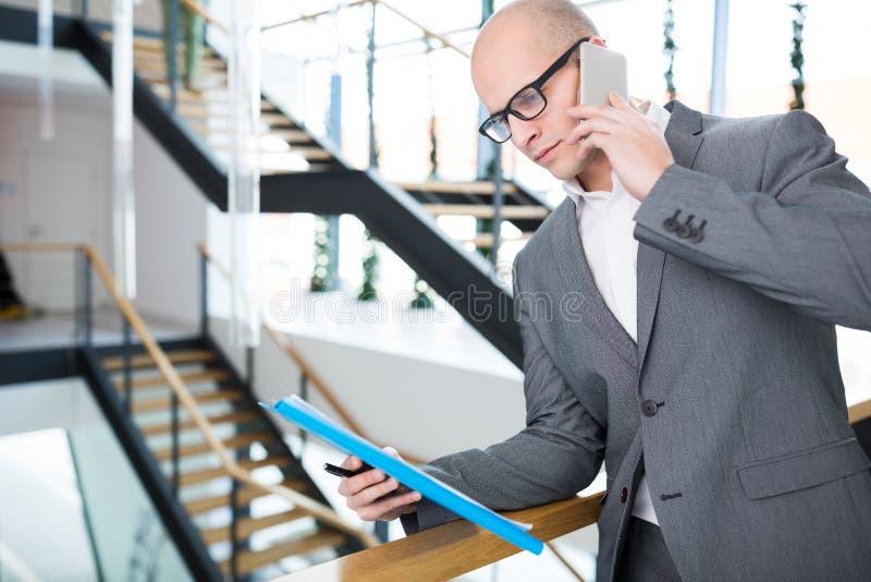 Homem de negócios With Clipboard Using Smartphone no escritório imagem de stock