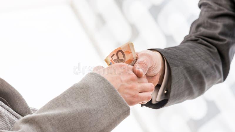 Homem de negócios com aperto de mão do dinheiro com sócio imagens de stock royalty free