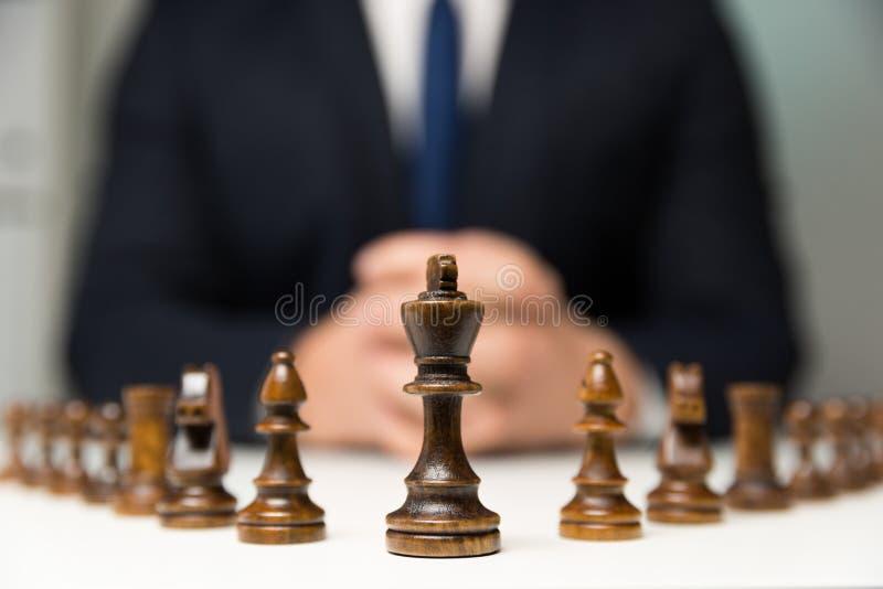 Homem de negócios com as mãos abraçadas que planeiam a estratégia com figu da xadrez fotografia de stock