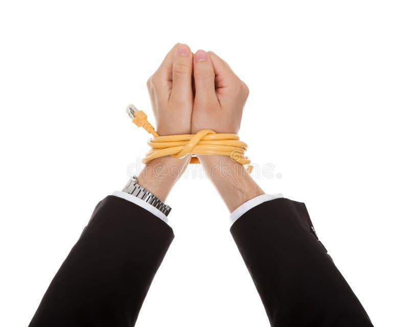 Homem de negócios com as mãos amarradas no cabo da rede fotografia de stock royalty free