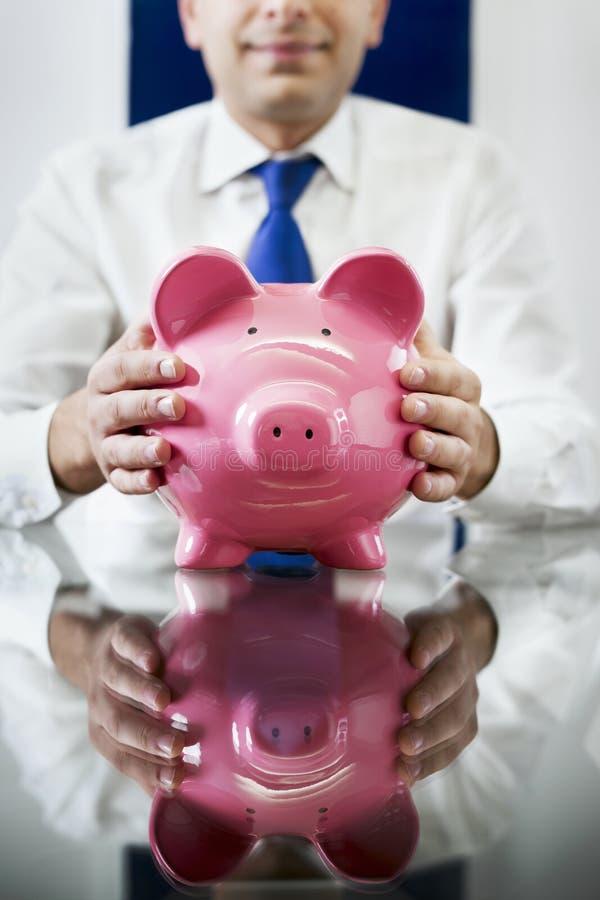 Homem de negócios com banco piggy fotografia de stock royalty free