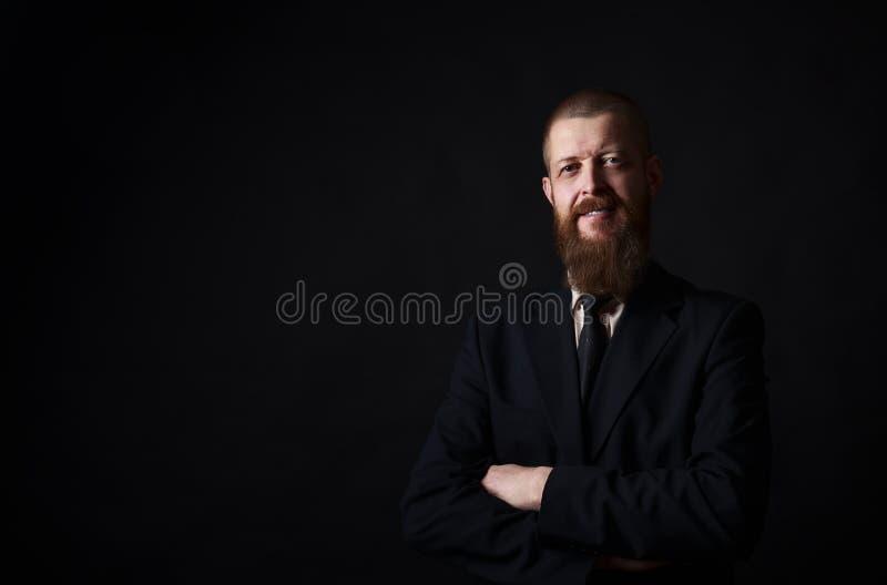 Homem de negócios com a barba que levanta na camisa preta no fundo escuro no estúdio lugar para a cópia-pasta imagens de stock