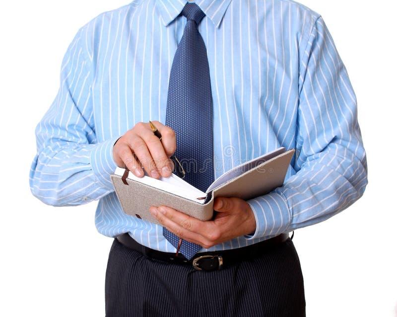 Homem de negócios com caderno e escrita da pena fotografia de stock