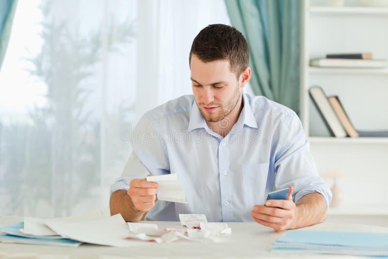 Homem de negócios com calculadora que verific contas fotos de stock